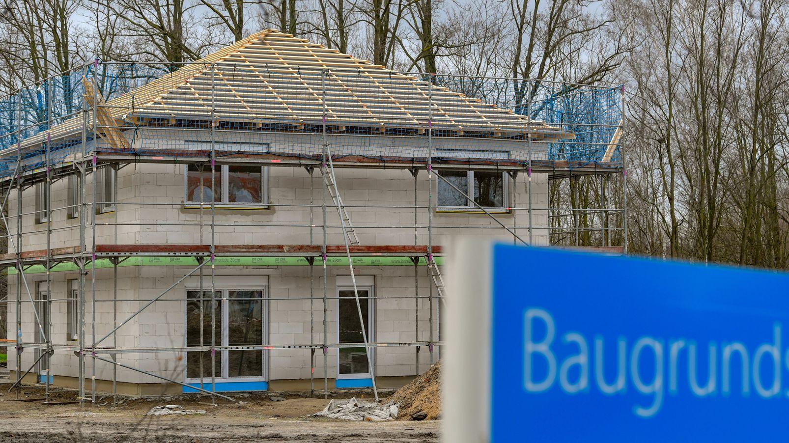 Ein Schild mit der Aufschrift «Baugrundstücke» steht am Rande eines Baufeldes mit einem Rohbau eines Eigenheimes.