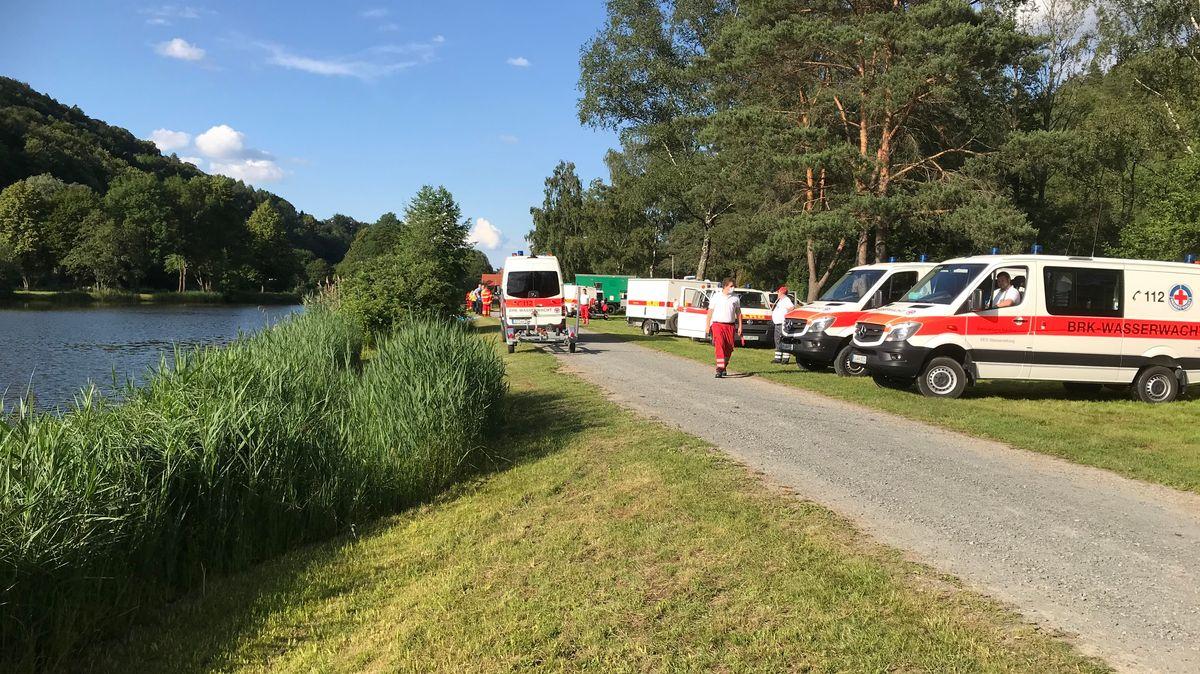 Rettungskräfte stehen am Ufer des Trebgaster Badesees.