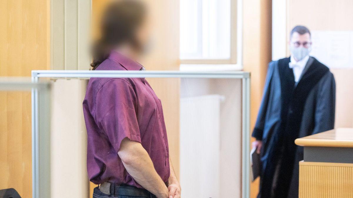 Ein Mann, stehend, in einem Gerichtssaal, im Hintergrund ein weiterer Mann in einer schwarzen Robe.