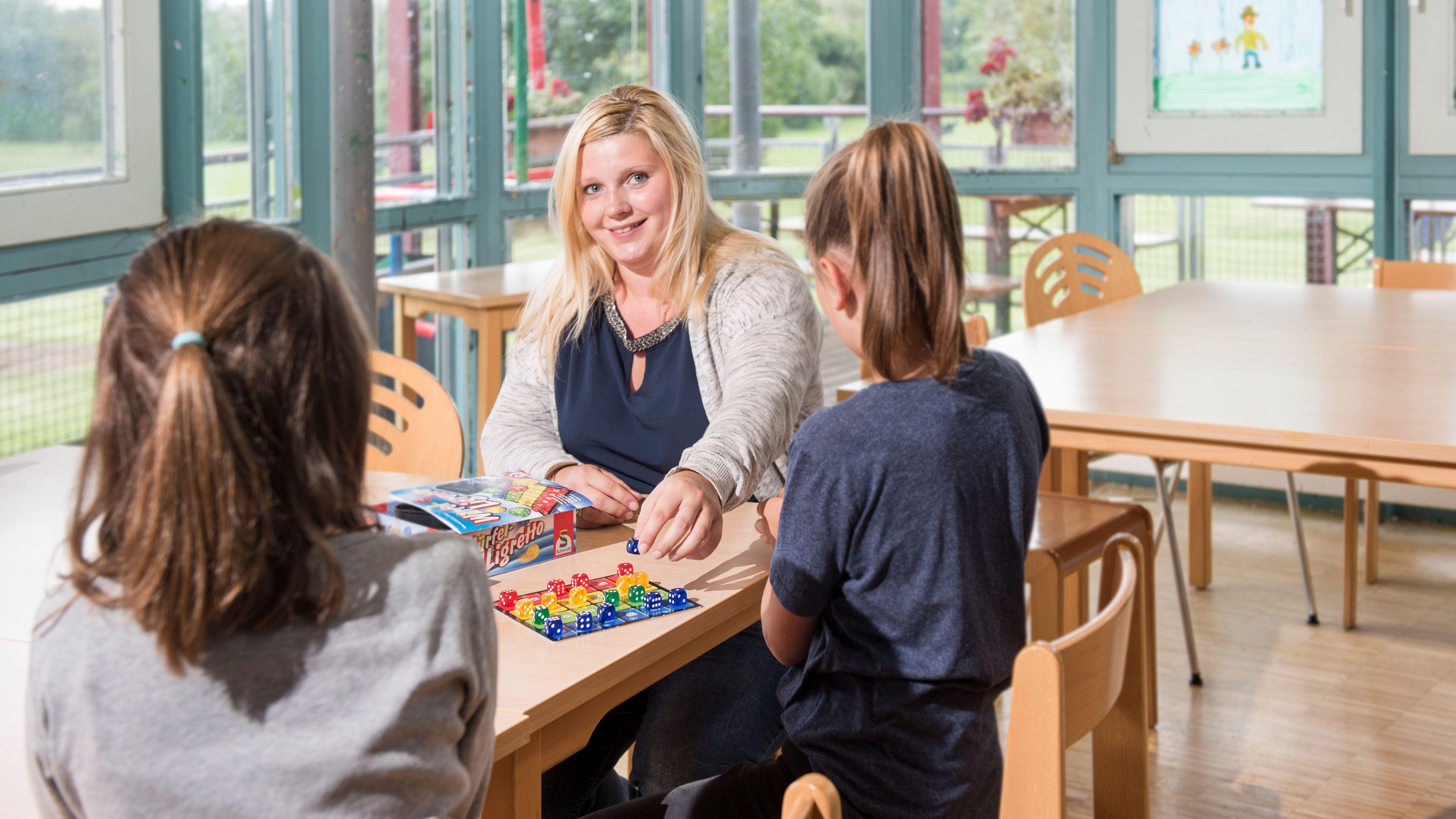 Eine Betreuerin sitzt mit zwei Kindern an einem Tisch und spielt mit ihnen ein Würfelspiel.