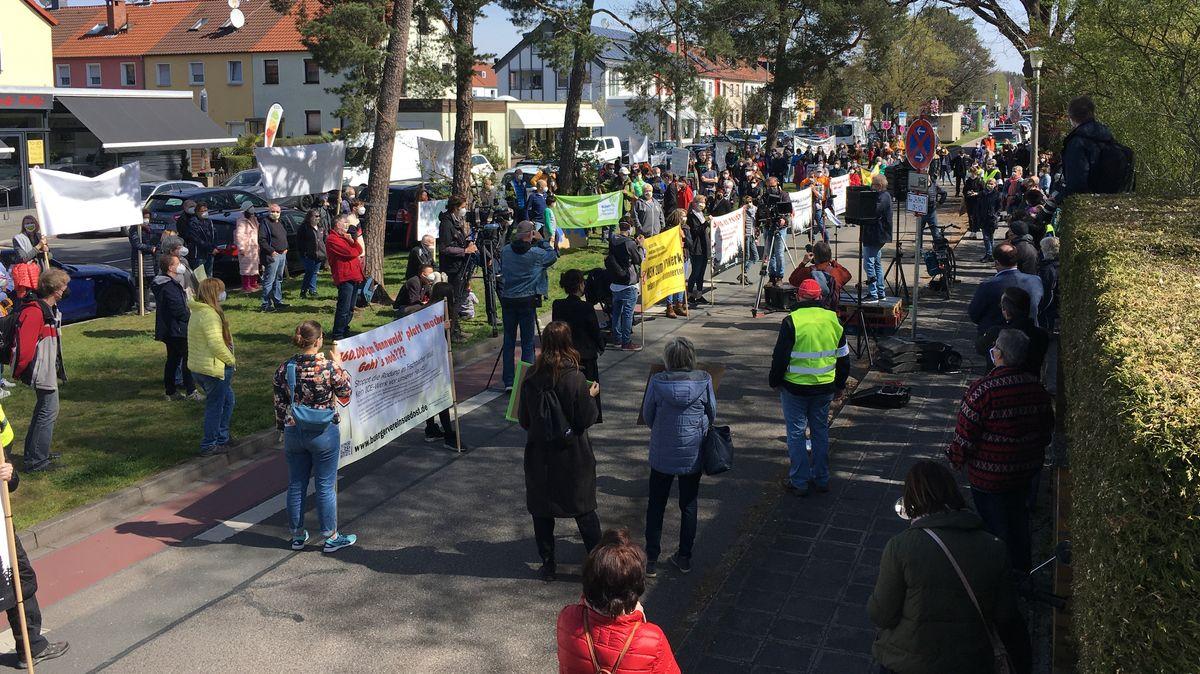 Menschen mit Plakaten stehen mit Abstand auf einer Straße