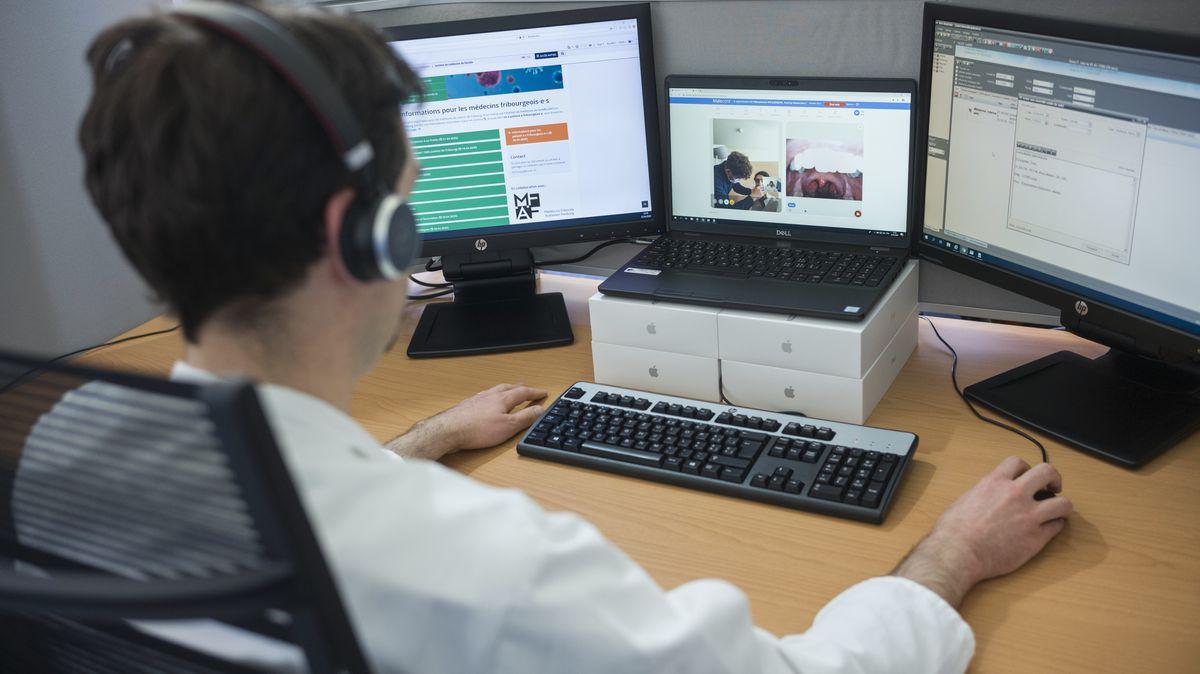 Ein Mediziner sitzt vor einem Computer und behandelt online einen Patienten