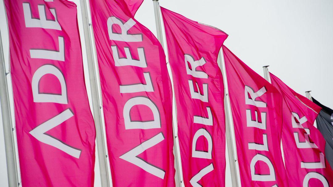 """Fahnen wehen an einer Filiale des Textilhändlers """"Adler Ihr Modemarkt""""."""