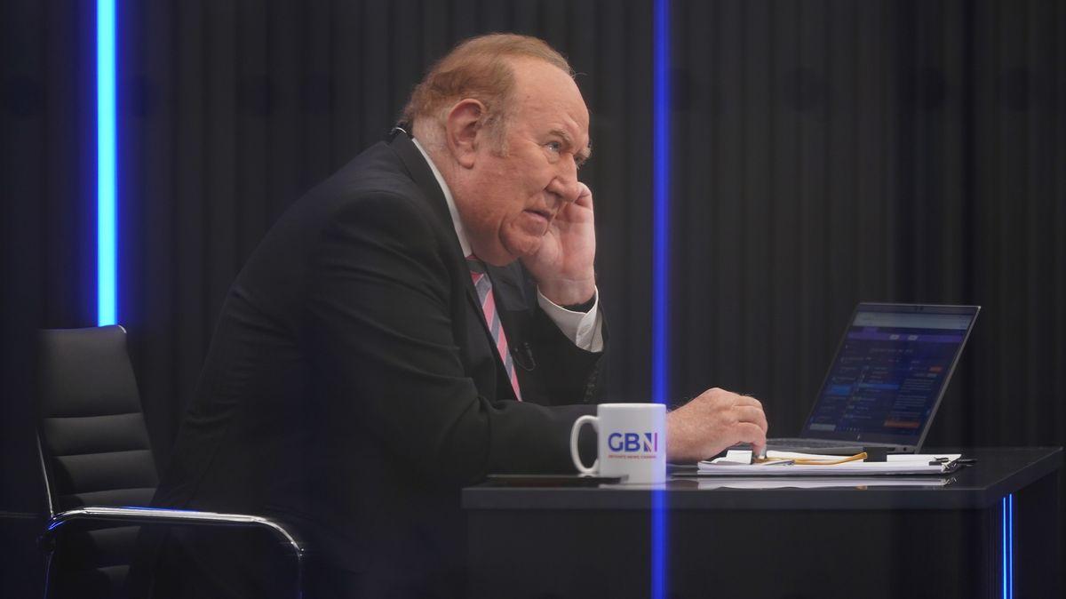 Der TV-Moderator am Tisch mit Laptop und Kaffeetasse