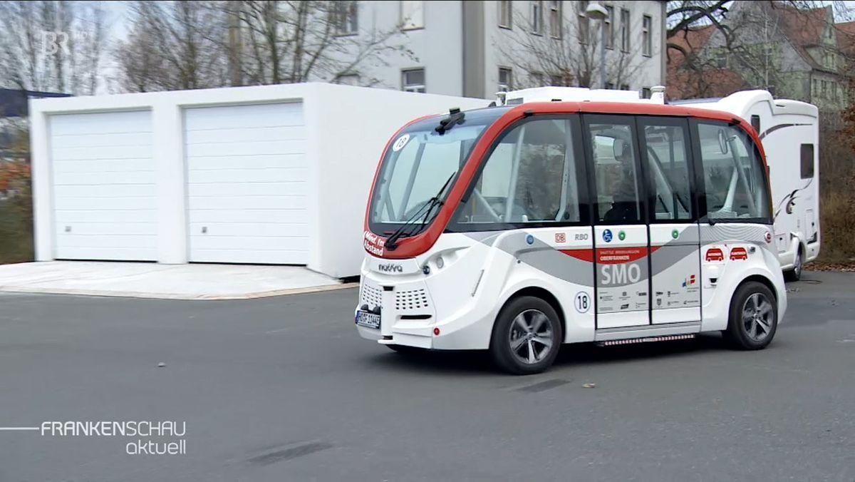 Ein weiß-roter Mini-Elektrobus faärt über einen aspahltierten Platz.