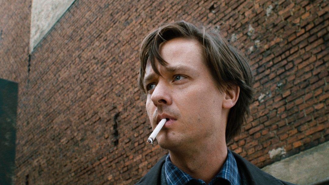 Ein junger Mann mit Zigarette im Mund vor einer rötlichen Backsteinmauer