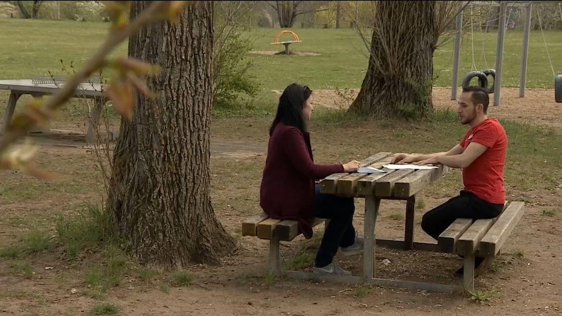 Zwei Menschen sitzen an einem Tisch im Park
