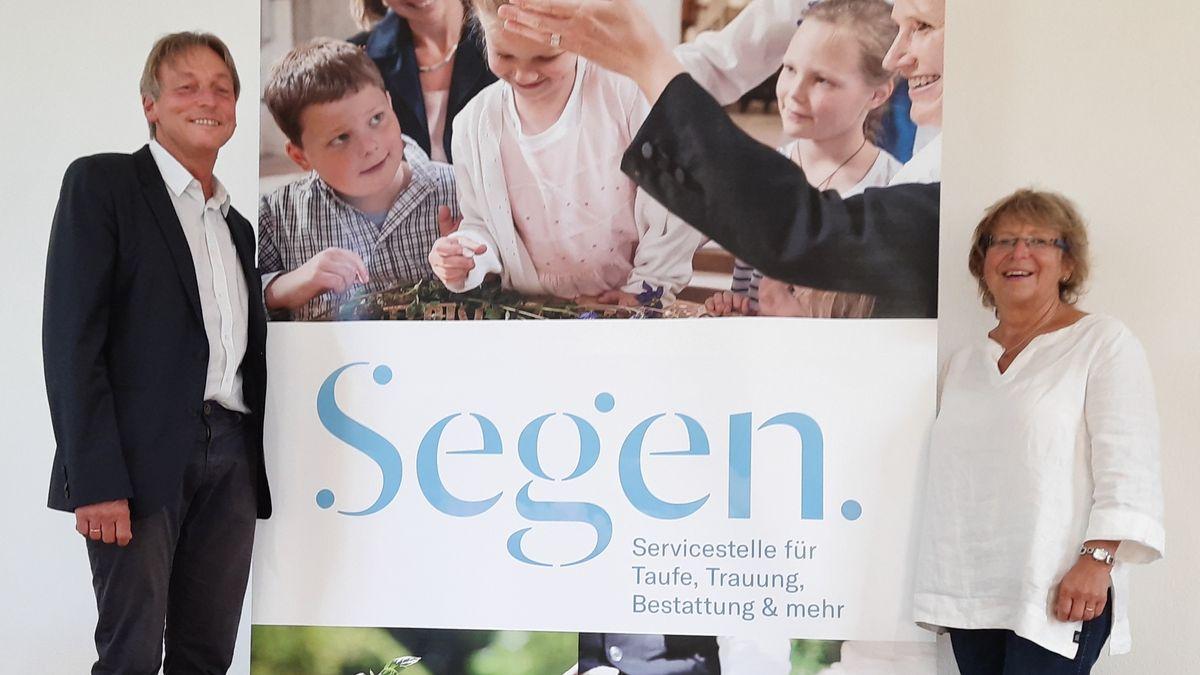 """Pfarrer Oliver Schürrle und Pfarrerin Karola Schürrle mit dem Logo der """"Segen-Servicestelle"""""""