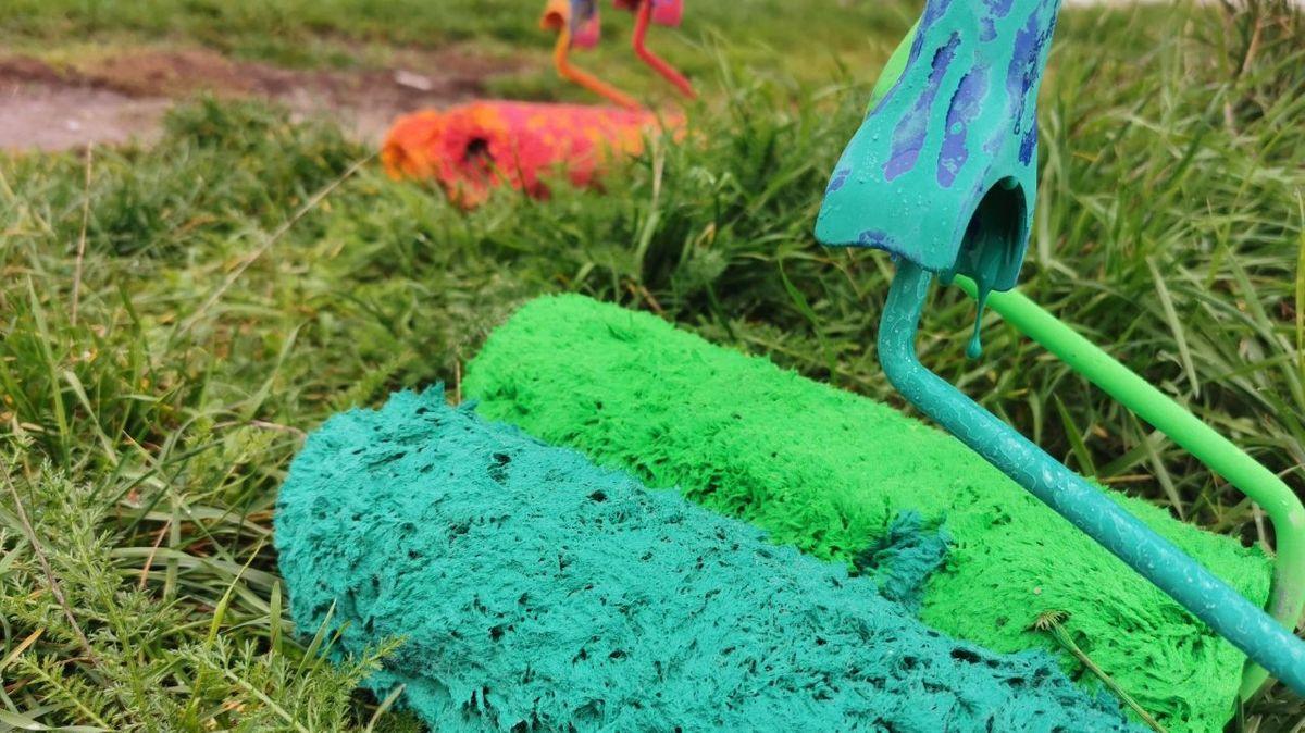 Verschiedenfarbige Farbrollen liegen im Gras