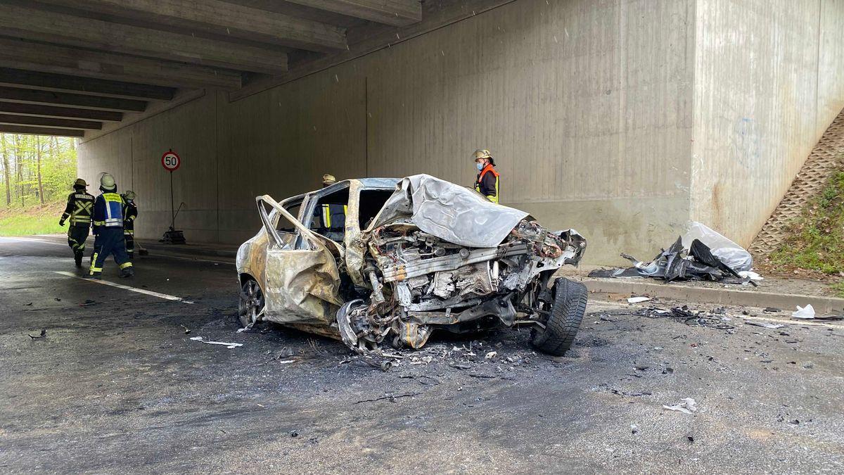 Ein demoliertes und ausgebranntes Autowrack steht unter einer Autobahnbrücke.