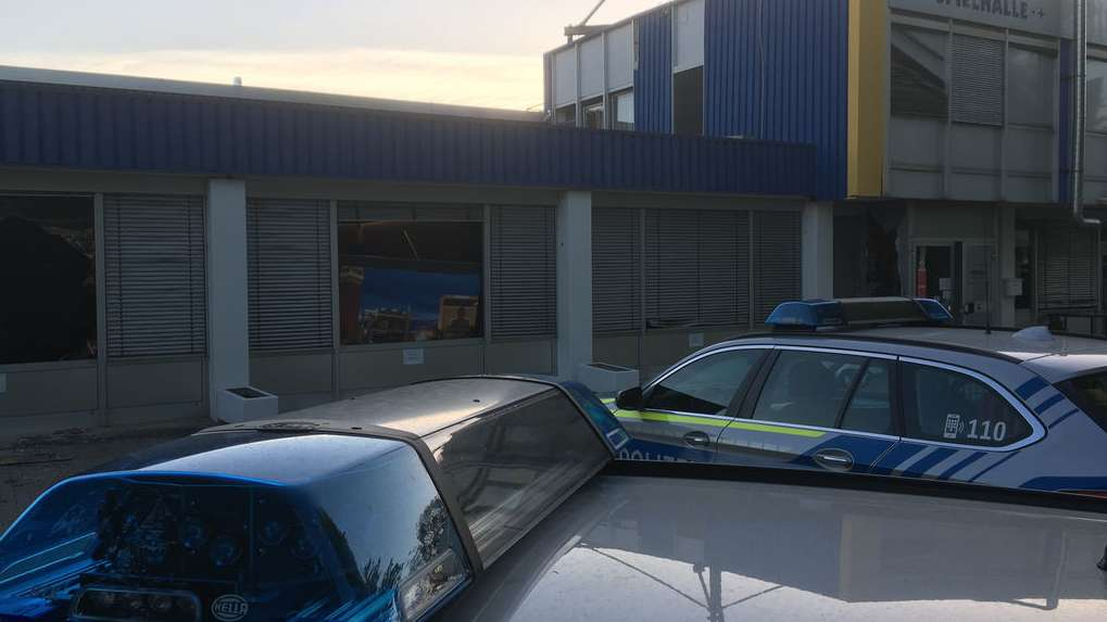 Polizeiautos vor einem beschädigten Gebäude