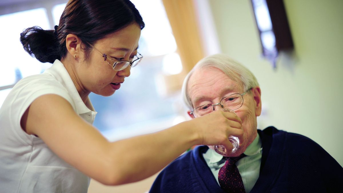 Pflegerin reicht einem alten Menschen das Trinkglas. (Symbolbild)