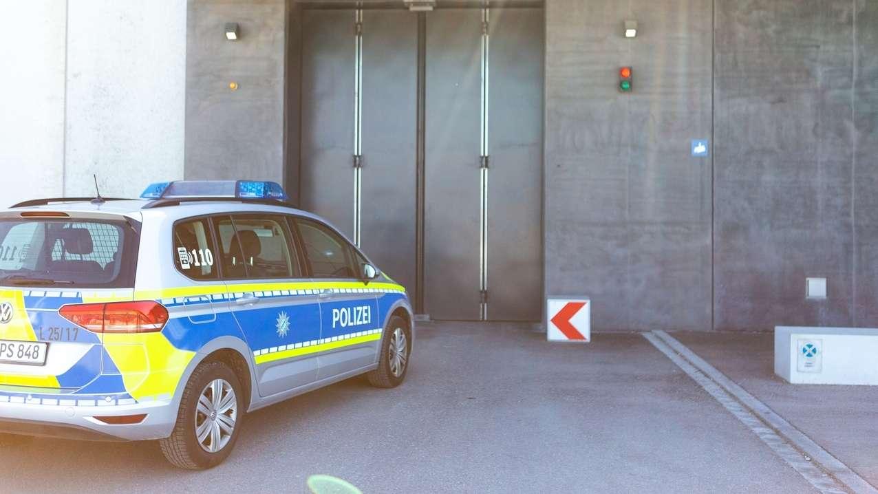 Ein Polizeiauto steht vor einem Gefängnistor. (Symbolbild)