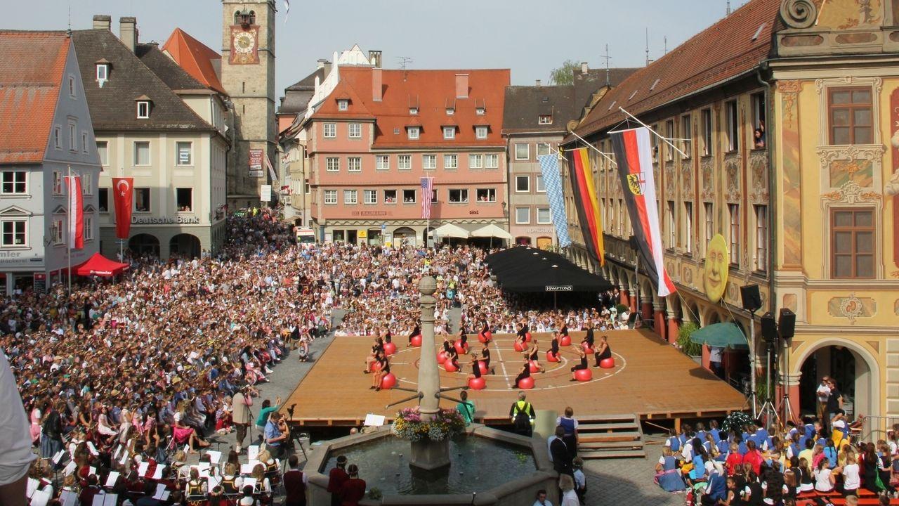 Auf dem Memminger Marktplatz haben sich viele Menschen versammelt, die den Kindern bei einer Aufführung zuschauen.