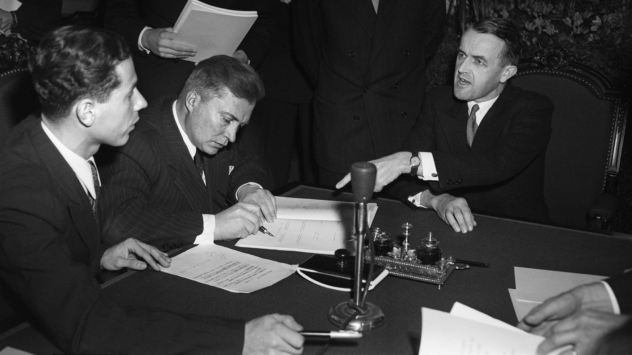 Am 12.8.1949 zeigt der Schweizer Bundesrat Max Petitpierre (r) dem Chefdelegierten der Sowjetunion, General Nikolai Slawin (m), wo er unterzeichnen soll.