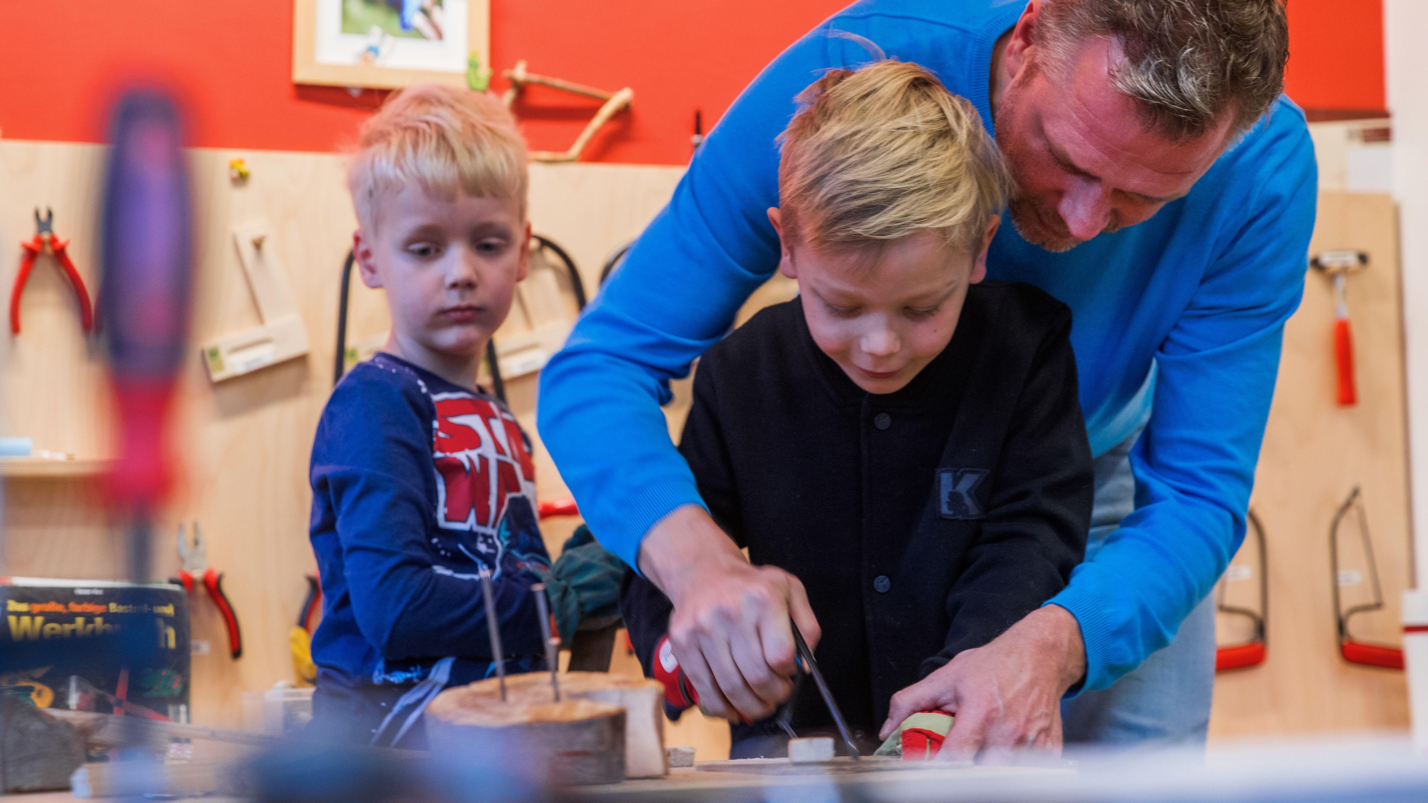 Ein Erzieher bastelt mit Kindern in einer Kindertagesstätte in der Holzwerkstatt (Symbolbild)