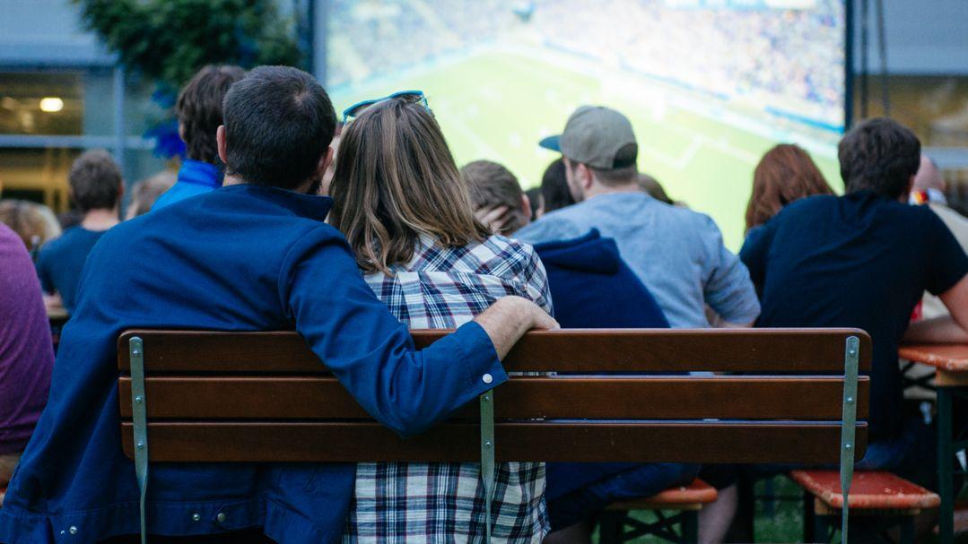 Fußballfans schauen ein Fußballspiel auf einer Großbildleinwand.