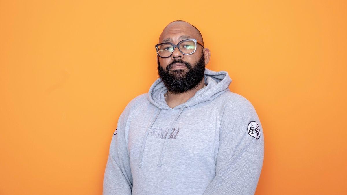 Journalist, Autor und Musiker David Mayonga, auch bekannt als Roger Rekless, in grauem Hoodie vor orangefarbener Wand