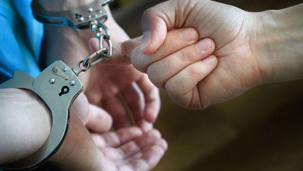 Eine Person in Handschellen wird abgeführt.