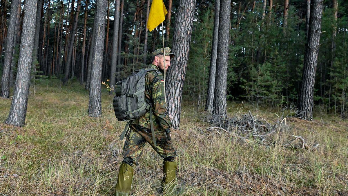 Ein Soldat steht im Wald mit einer gelben Fahne in der Hand.