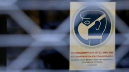 Ein Schild, das auf die Schutzmaskenpflicht in einem Geschäft hinweist, hängt hinter einem Gitter. | Bild:dpa-Bildfunk