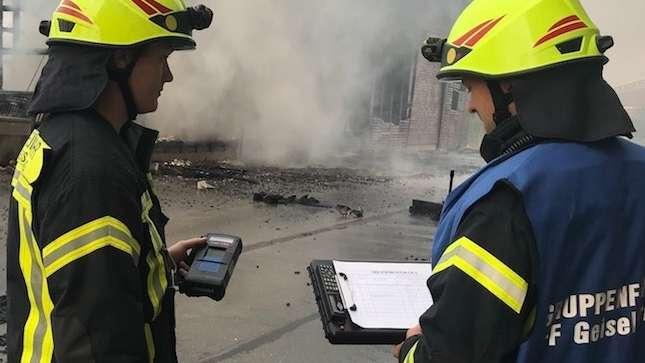Zwei Feuerwehr-Männer halten ein Messgerät und einen Notizbuch in der Hand, sie sind von hinten zu sehen.