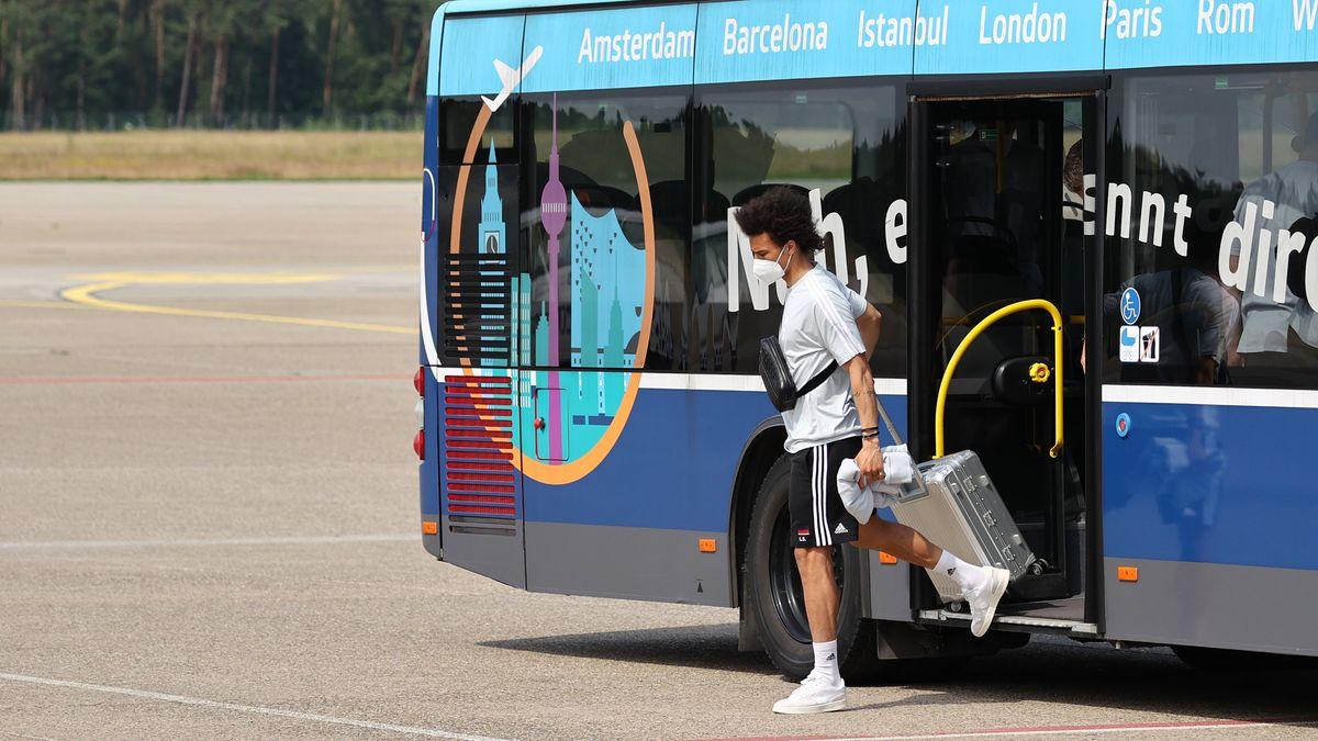Leroy Sane steigt aus einem Bus, in der Hand einen silbernen Rollkoffer.