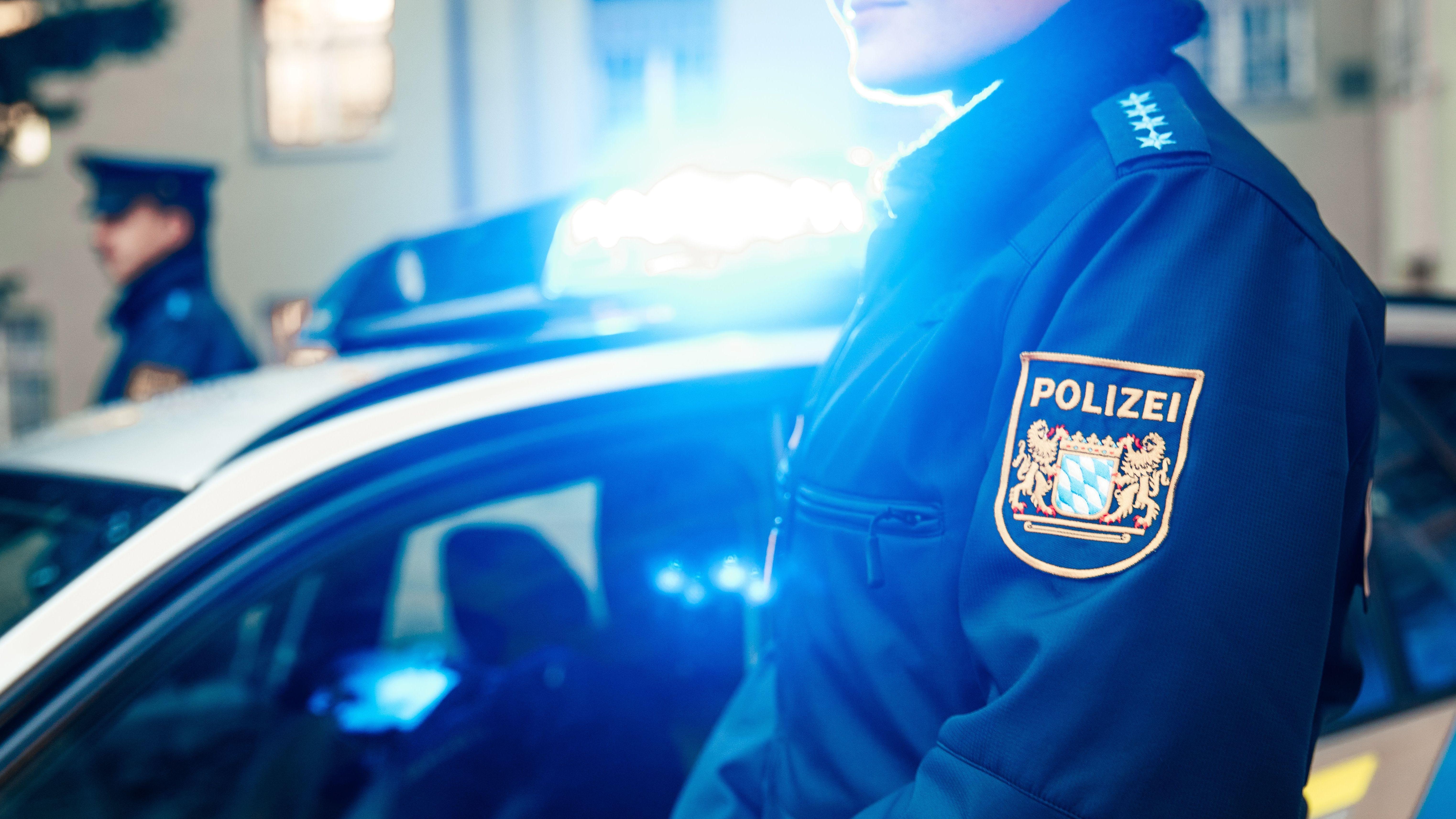 Polizistin und Polizist vor einem Polizeiauto mit Blaulicht