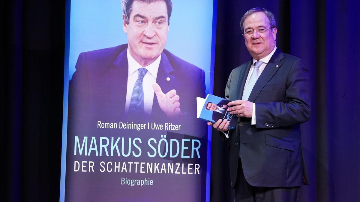 Armin Laschet neben einer übergroßen Markus Söder-Biografie.