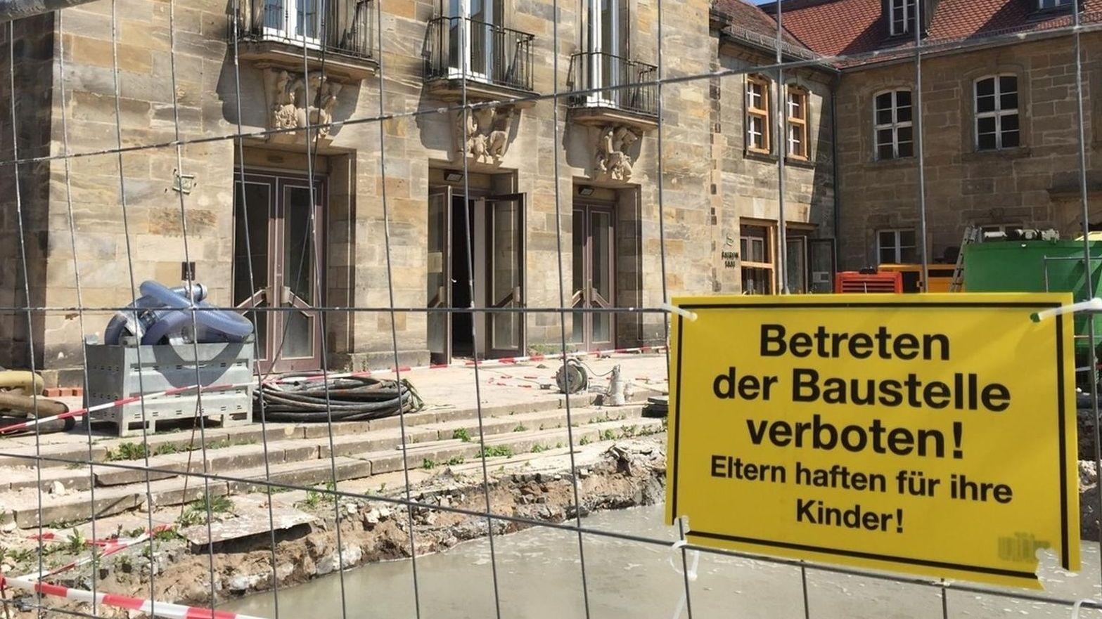 """Die ehemalige Stadthalle Bayreuth, davor ein Bauzaun mit einem gelben Schild, auf dem """"Betreten der Baustelle verboten"""" steht."""