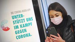Frau mit Handy vor Corona-Warn-App-Plakat (Symbolbild).   Bild:Picture Allaince