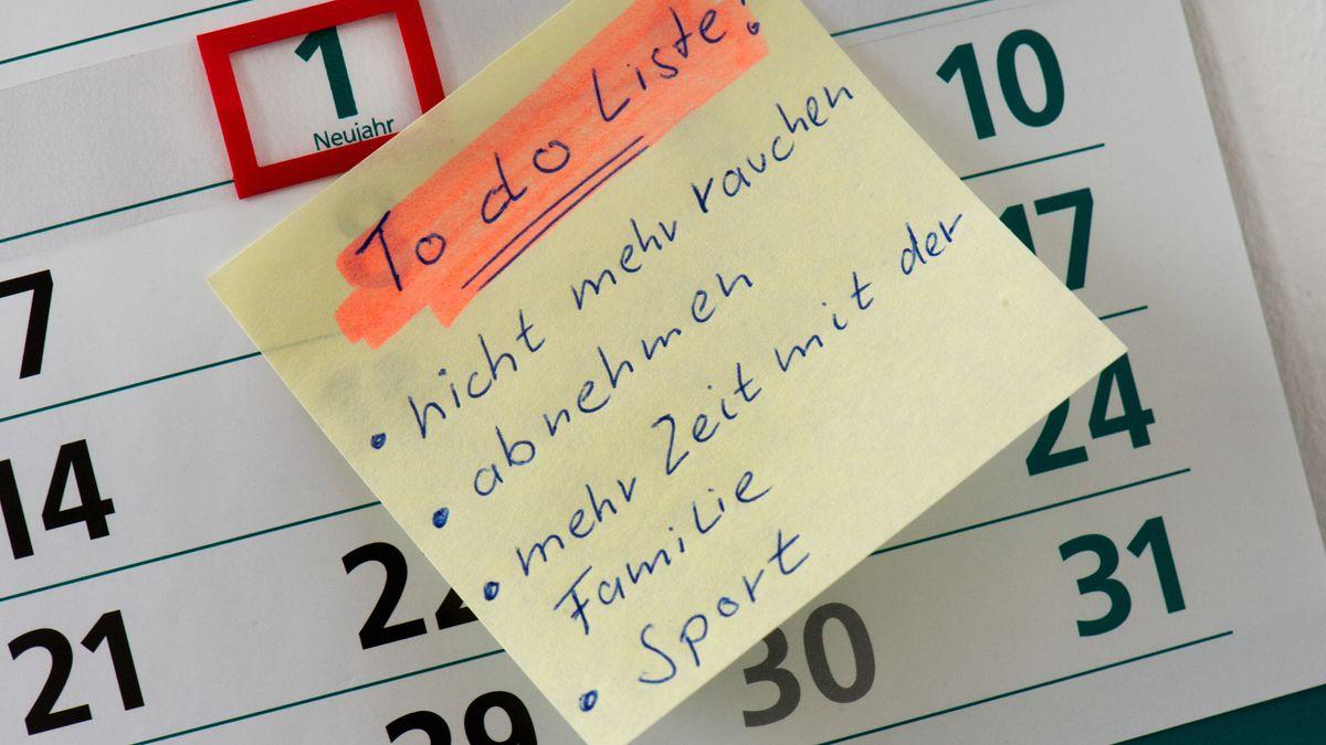 """Zettel mit  """"To do Liste"""" auf dem 1. Januar eines Kalenders mit den Vorsätzen """"nicht mehr rauchen, abnehmen, mehr Zeit mit der Familie und Sport""""."""