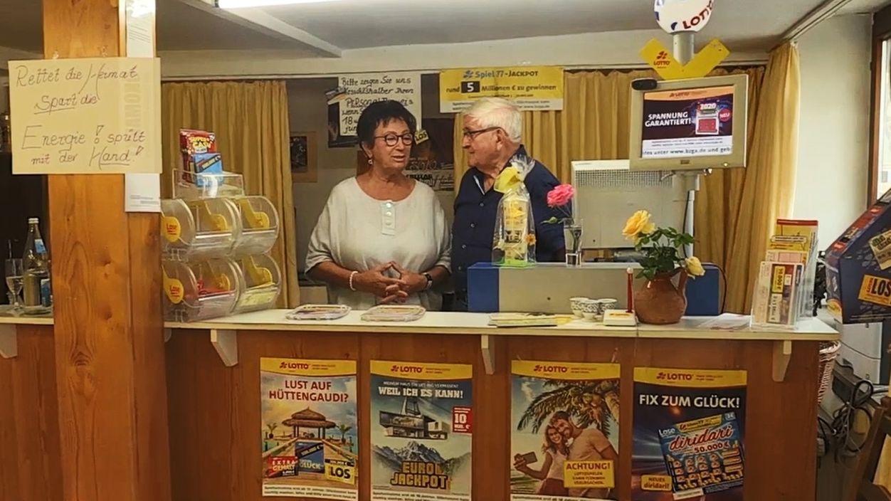 Eine Frau und ein Mann stehen hinter einem Tresen in einem Lottoladen.