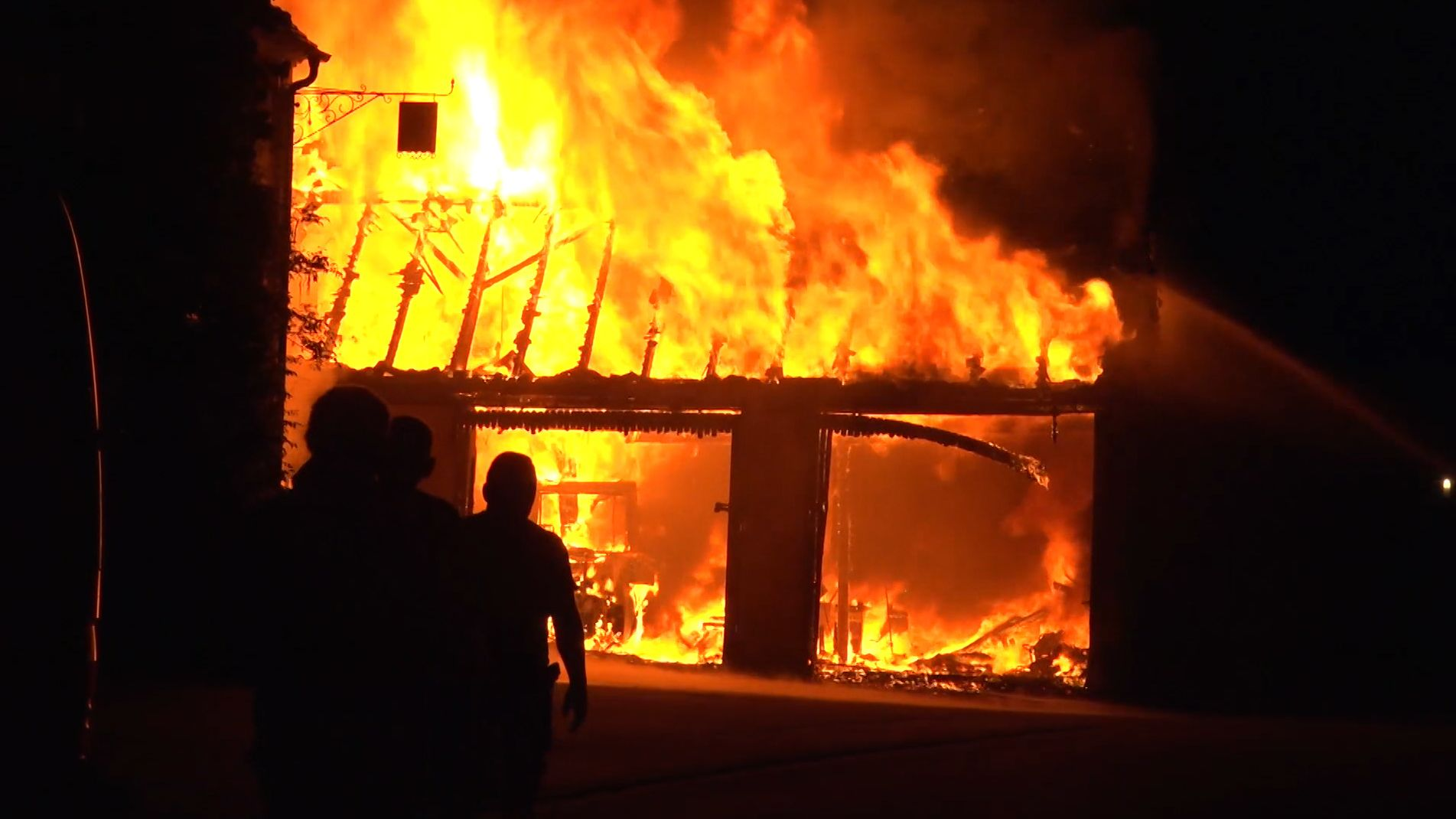 Silhouetten von Männern vor einer lichterloh brennenden Scheune