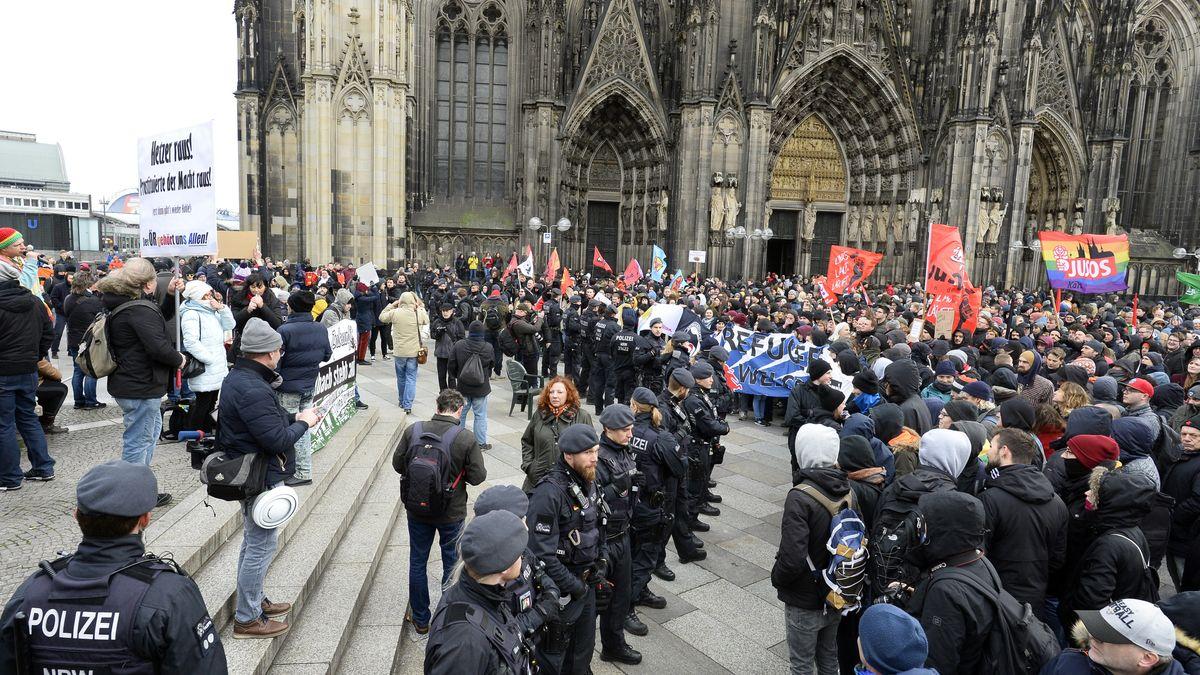"""Rechte Demonstranten (l.) und von """"Köln gegen rechts"""" stehen einander am 4.1.20 auf dem Dom gegenüber. Die Polizei trennt die Lager."""