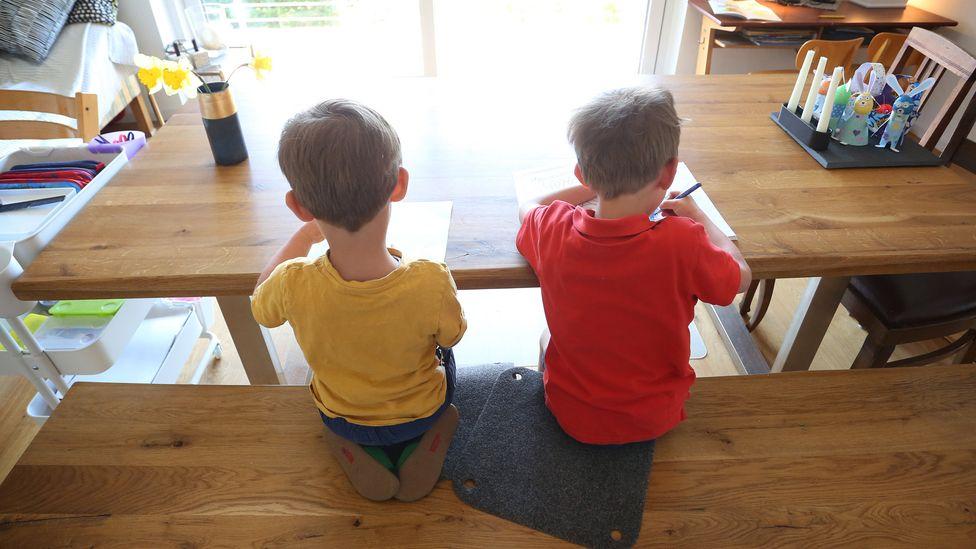 Zwei Jungen füllen zuhause Lernbücher aus.