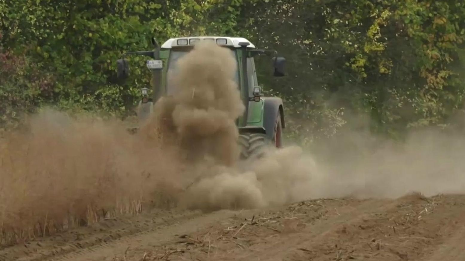 Ein Traktor fährt über ein Feld und wirbelt Staub auf