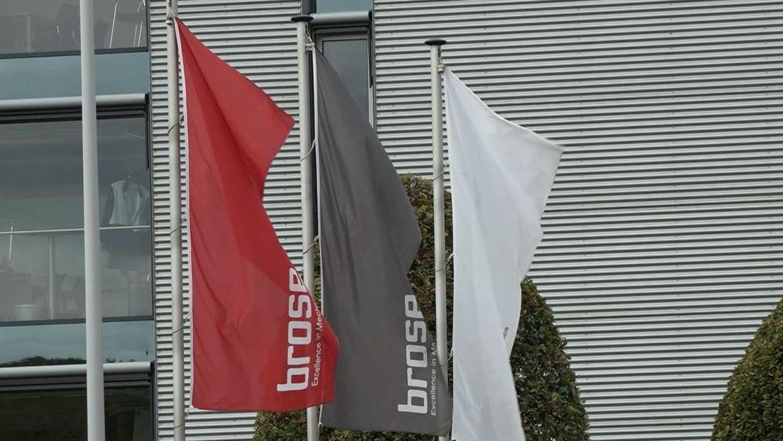 """Eine rote, eine graue und ein weiße Fahne mit der Aufschrift """"Brose"""" hängen vor einem Firmengebäude."""