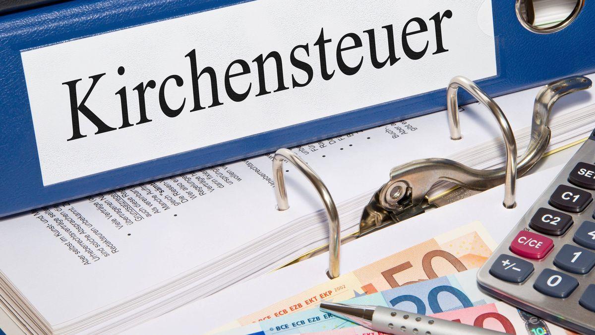 Ein Ordner mit der Aufschrift Kirchensteuer liegt mit einem Taschenrechner und Euro-Scheinen auf einem weiteren aufgeschlagenen Ordner.
