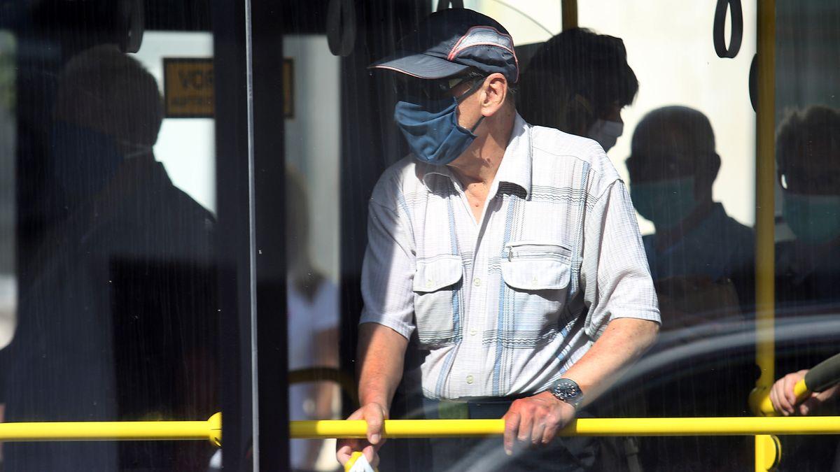 Fahrgast mit Mund-Nasen-Bedeckung in einem Bus (Symbolbild)