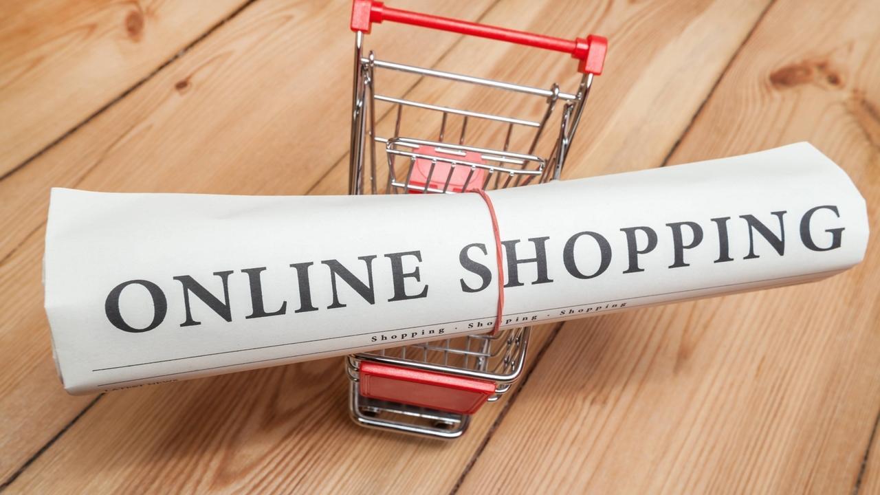 """Ein Einkaufswagen in Miniaturform, auf dem eine eingerollte Zeitung mit der Aufschrift """"Online Shopping"""" liegt."""