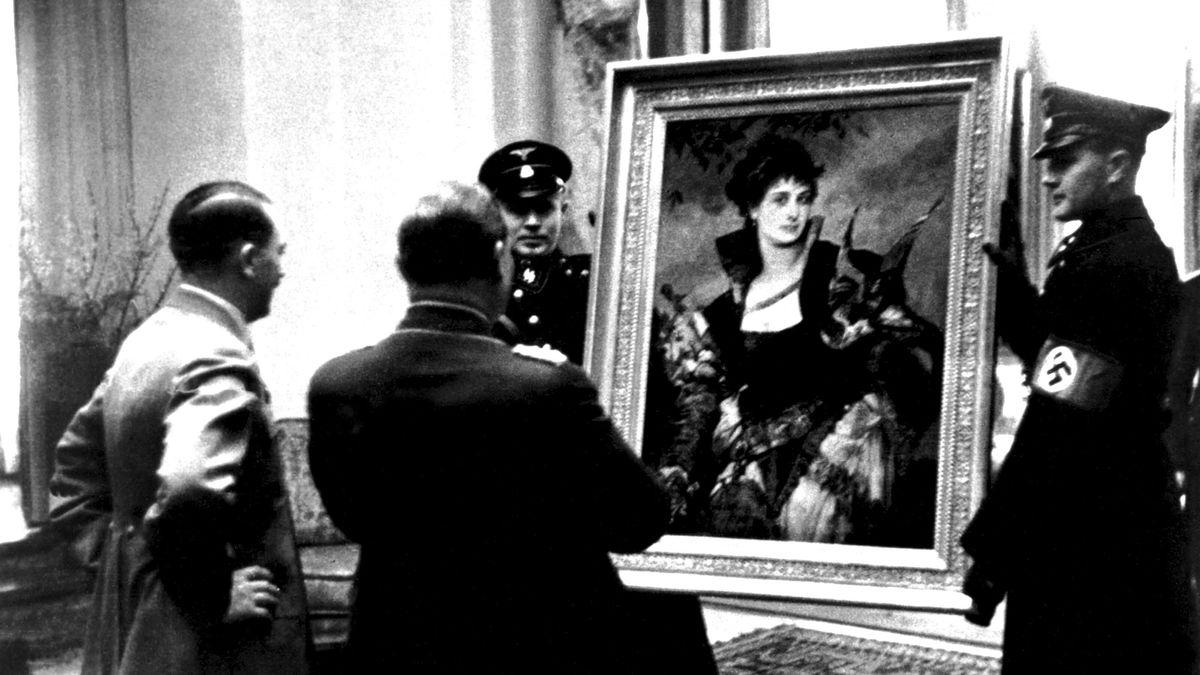 Die mit dem Rücken zum Betrachter stehenden Hitler und Göring betrachten ein großformatiges, gerahmtes und von zwei Soldaten präsentiertes Gemälde, das eine Falknerin zeigt