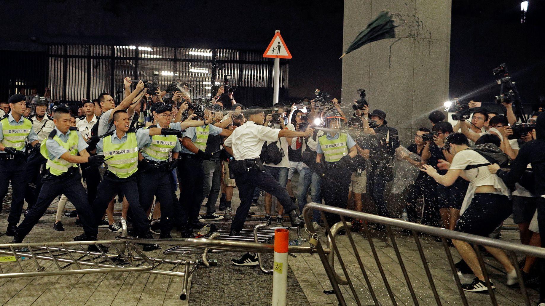 Polizisten in Hongkong sprühen Pfefferspray auf Demonstranten, die gegen das von der Regierung geplante Auslieferungsgesetz protestieren.