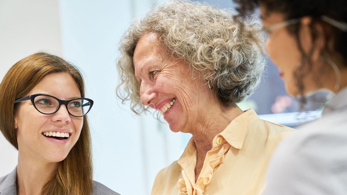 Junge Business Frauen im Gespräch mit einer älteren Kollegin im Business Team