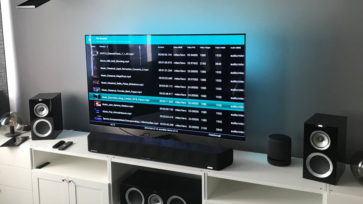 Bildschirm auf Sideboard zeigt Musiktitel, daneben stehen Lautsprecher.