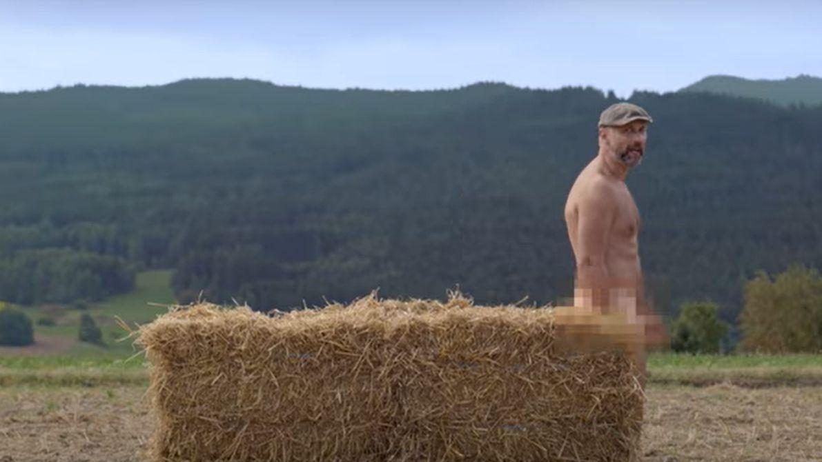 Ein Mann steht nackt hinter einem Heuballen.