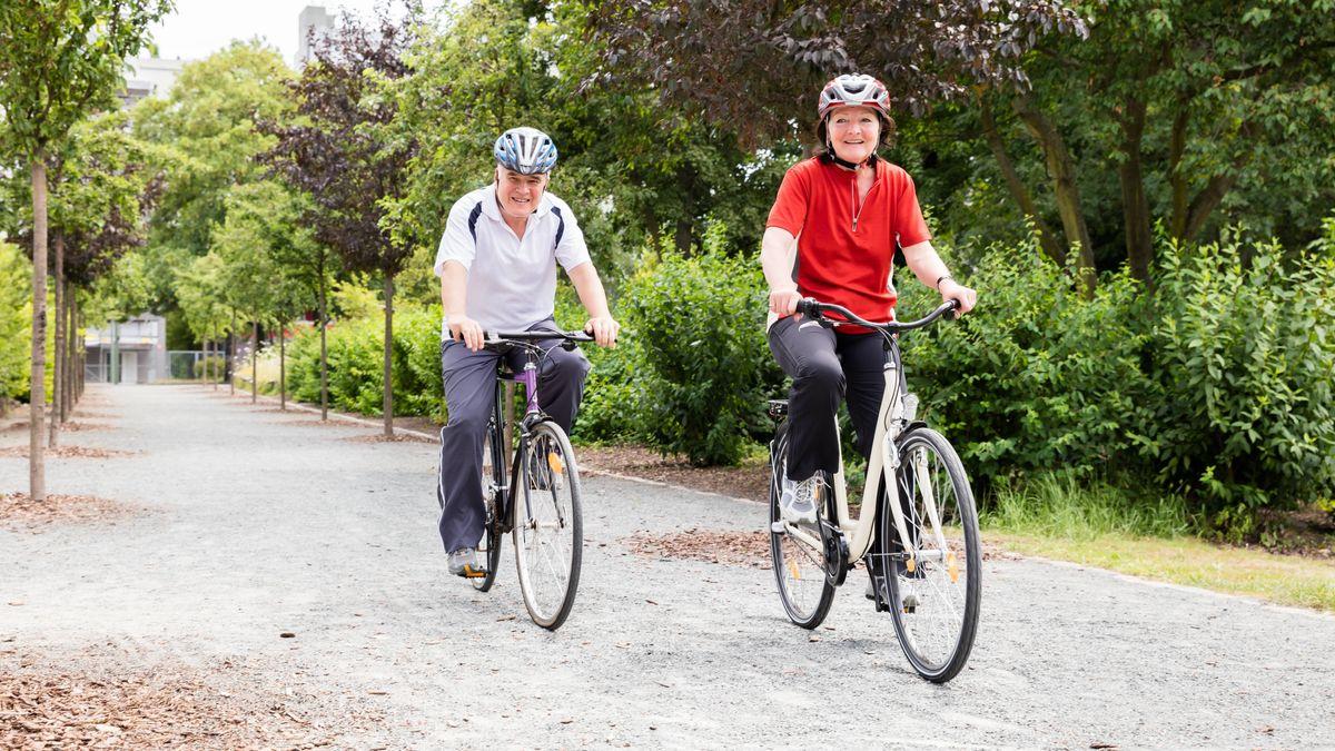 Ein älteres Ehepaar fährt auf Fahrrädern durch ein Park (Symbolbild)