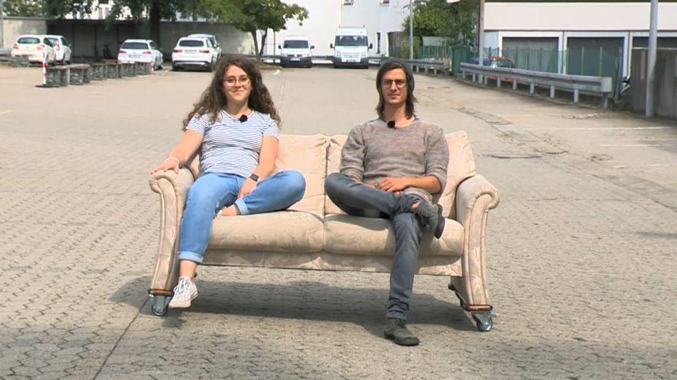 Lena Jungkunz und Lukas Lauterbach sitzen auf einer Couch, die auf der Straße steht, im Hintergrund Autos.