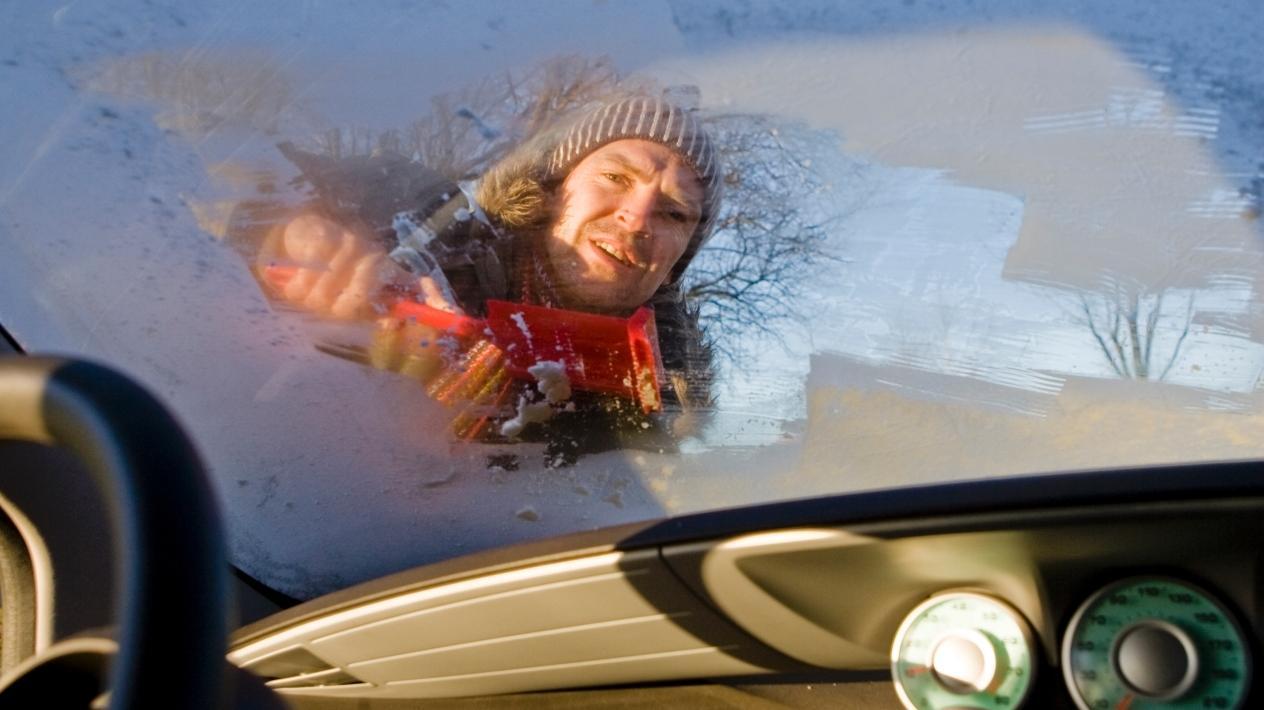 Mann kratzt seine Autoscheibe frei