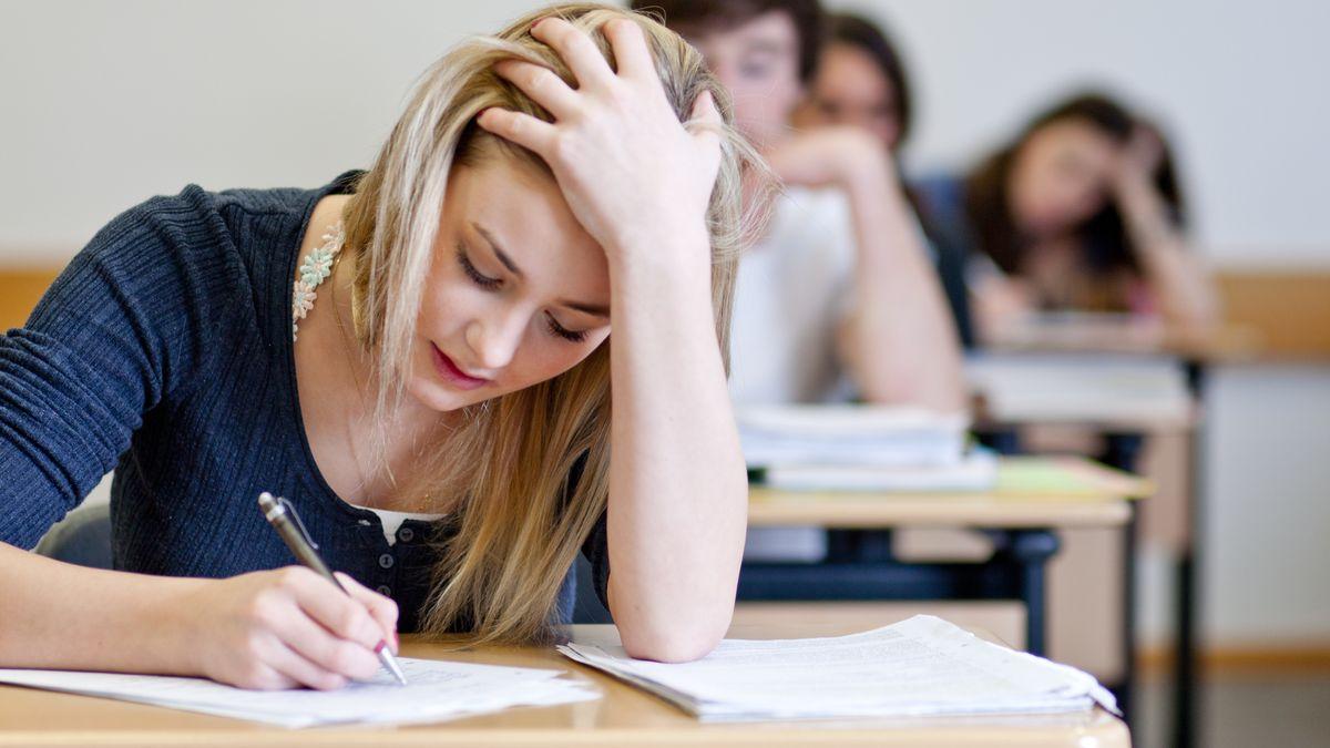 Eine junge Frau schreibt eine Klausur (Symbolbild)